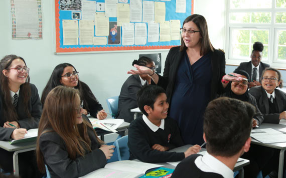 A teacher with her students, smiling in a classroom