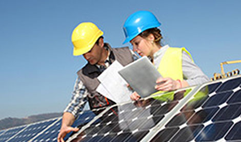 man and woman in hard hats looking at solar panels