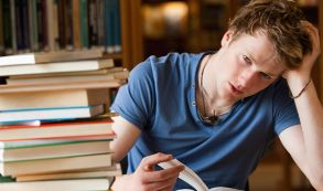 Male student studying amongst books