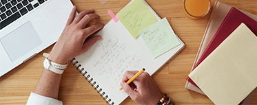 Writing in notepad by laptop Discover our AS and A-level teaching resources