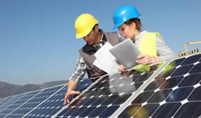 Two professionals inspecting solar panels