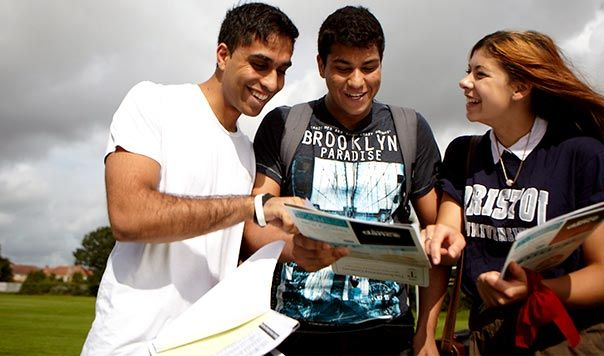 Three students outside together looking at documents
